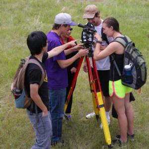 students using survey equipment